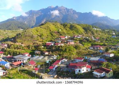 Beautiful panorama view of rocky mountain range Mount Kinabalu with tropical landscape during morning with homestay native village at Kundasang Sabah Malaysia.