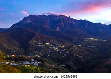 Beautiful panorama view of rocky mountain range Mount Kinabalu with tropical landscape during morning with homestay and green vegetation at foreground. Mount Kinabalu view in Kundasang Sabah Malaysia