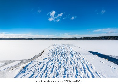 Beautiful panorama winter landscape view of blue sky and frozen snow lake and a jetty with footprints in the snow.