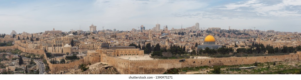 Beautiful panoramic aerial view of the Old City, Tomb of the Prophets and Dome of the Rock during a sunny and cloudy day. Taken in Jerusalem, Capital of Israel.