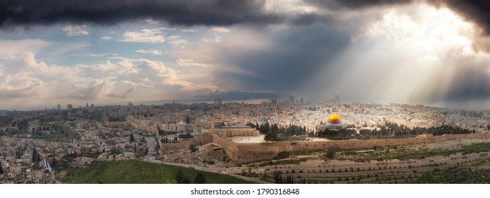 Beautiful panoramic aerial view of the Old City, Tomb of the Prophets and Dome of the Rock. Dramatic Sky with Sunrays Composite. Jerusalem, Capital of Israel.