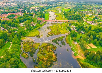 Beautiful panoramic aerial view photo from flying drone to Venta Rapid waterfall,the widest waterfall in Europe and the third longest brick bridge in Europe on a summer day in Kuldiga, Latvia.(series)