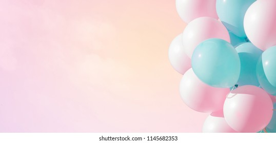 Beautiful panoramic background with pink and blue balloons. Group of pastel party balloons on soft background. Concept of happiness, joy, birthday. Wide Angle Holiday Web Banner With Copy Space