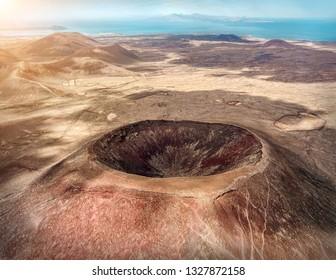 Beautiful panoramic birds eye view on Calderon Hondo, Fuerteventura island. Aerial shooting vulcano around mountains with ocean coastline at sunny day. Travell, Mountains, nature, freedom concept.