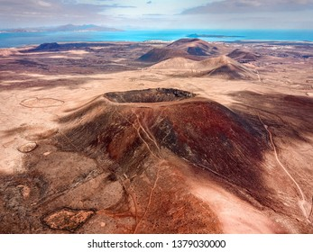 Beautiful panoramic birds eye view on Calderon Hondo, Fuerteventura island. Aerial shooting vulcano around mountains with ocean coastline at sunny day. Travell, Mountains,islands, nature concept.