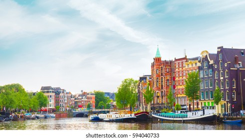Beautiful panoramic cityscape of Amsterdam, capital of Netherlands. Colorful view of the canal with an amazing building in summer. Horizontal Image.