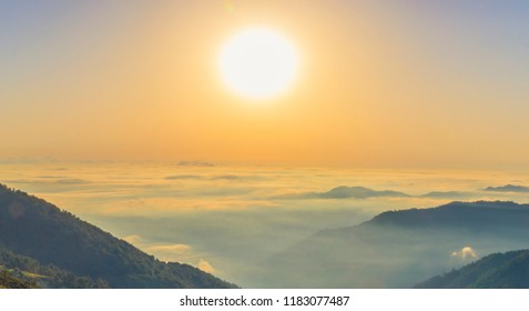 Beautiful panoramic landscape above clouds and mountains with sun rising in the middle.