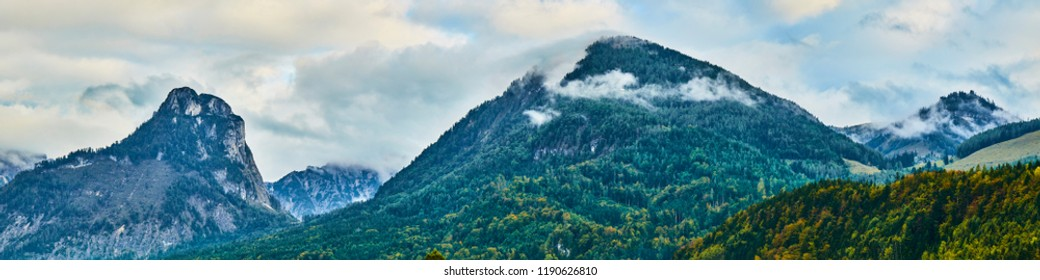Beautiful panoramic landscape with colorful forests, Alpine mountains and dramatic sky near Wolfgangsee lake in Austria.