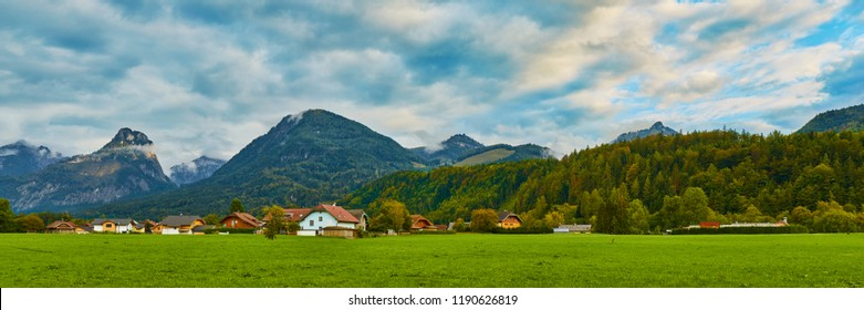 Beautiful panoramic landscape with lush green grass land and Alpine mountains near Wolfgangsee lake in Austria.