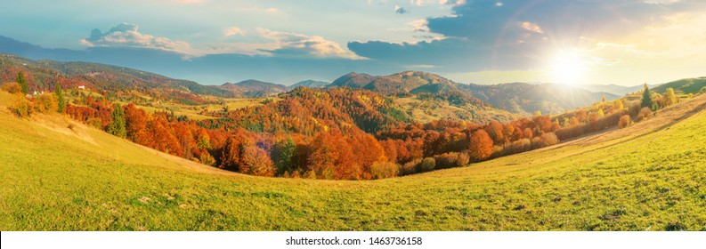 beautiful panoramic landscape in october at sunset. meadow in weathered grass trees in fall foliage. mountain range in the distance beneath a sky with fluffy clouds in evening light