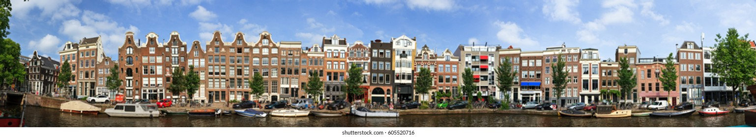 Beautiful panoramic linear panorama of the UNESCO world heritage Prinsengracht canal  in Amsterdam, the Netherlands, on a sunny summer day with a blue sky and clouds
