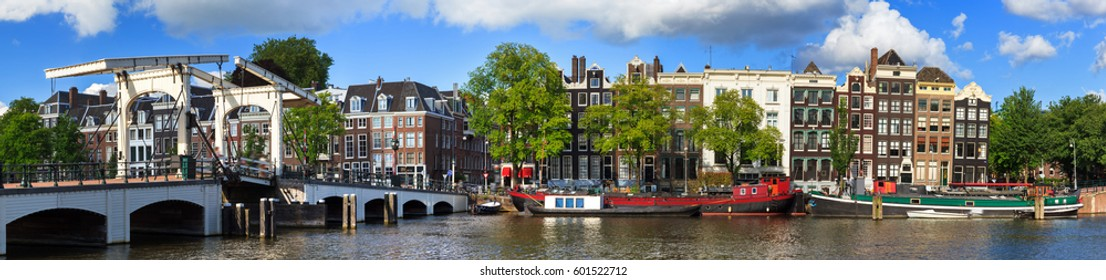 Beautiful panoramic panorama of the skinny bridge (magere brug) over the river Amstel in Amsterdam, the Netherlands, on a sunny summer day with some clouds