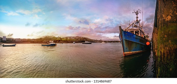 Beautiful panoramic sunset landscape in a Castletownbere town. Ships and boats in the evening.View from the harbor. County Cork, Ireland