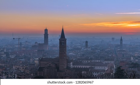 Beautiful panoramic sunset view of old town of Verona, Torre Lamberti and Santa Anastasia bell tower covered with evening fog. View from Piazzale Castel S. Pietro. Winter time. Verona, Italy