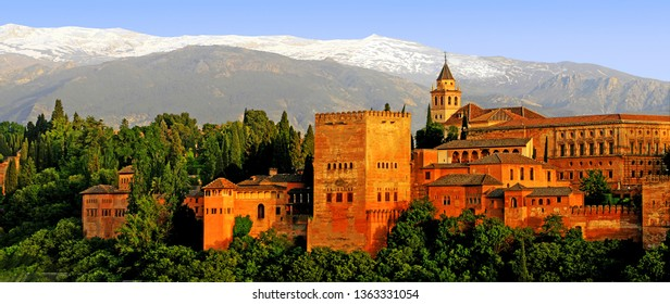 Beautiful panoramic view of the Alhambra or Red fortress, (UNESCO World Heritage Site), with Sierra Nevada mountains covered by snow and blue sky at sunset, Granada, Andalusia, Spain