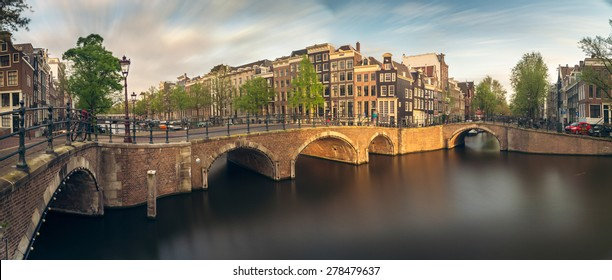 Beautiful panoramic view of Amsterdam canals with bridge and typical dutch houses. Holland, Netherlands, Europe