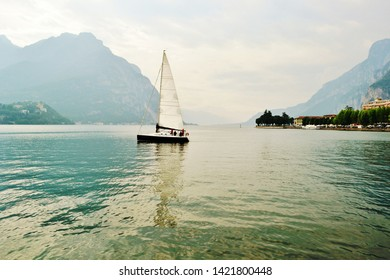 Beautiful panoramic view in backlit to the lake Como at Lecco with sailboat navigating from the city.