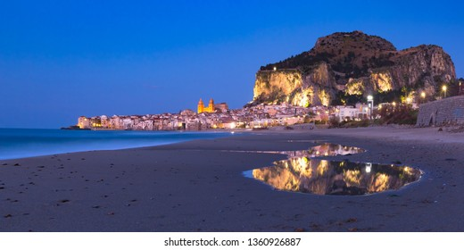 Beautiful panoramic view of the beach, Cefalu Cathedral and old town of coastal city Cefalu during evening blue hour, Sicily, Italy