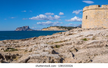 A beautiful panoramic view from the coastal town of Moraira, looking towards Calpe Rock and the town of Calpe in the Costa Blanca region of Spain. The Castle of Moraira is in the foreground.