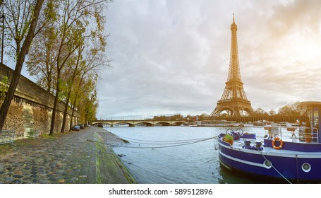 Beautiful panoramic view of the Eiffel Tower and Jena bridge from the river Seine embankment. Dramatic cloudscape. Traditional citycape in backlit morning sunbeam. Paris, France.