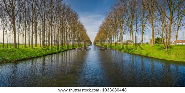 Beautiful panoramic view of famous Damme Canal, also known as Damse Vaart or Napoleonvaart, near the city of Brugge in beautiful evening light at sunset in springtime, West Flanders, Belgium
