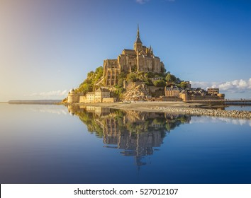 Beautiful panoramic view of famous Le Mont Saint-Michel tidal island with deep blue water and clear reflections in golden evening light at sunset in summer, Normandy, northern France