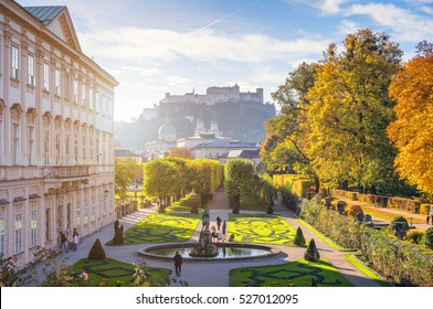Beautiful panoramic view of famous Mirabell Gardens with old historic fortress Hohensalzburg and church towers in idyllic golden morning light with blue sky at sunrise in fall, Salzburg, Austria