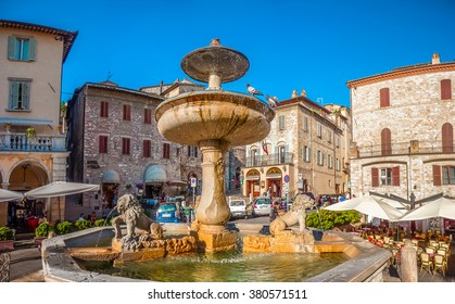 Beautiful panoramic view of famous Piazza del Comune with historic fountain figuring three lions and ancient palaces in the background on the main sqaure of Assisi, Umbria, Italy