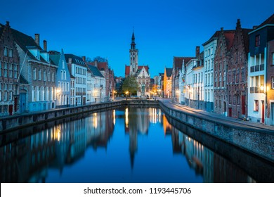 Beautiful panoramic view of famous Spiegelrei canal with famous Poortersloge and Jan van Eyck square in the background illuminated during blue hour at dusk, Brugge, Flanders region, Belgium