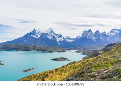 Beautiful panoramic view of golden grass and aqua blue Pehoe lake with small island with nature cuernos mountains peak with cloud in autumn, Torres del Paine national park, south Patagonia, Chile.