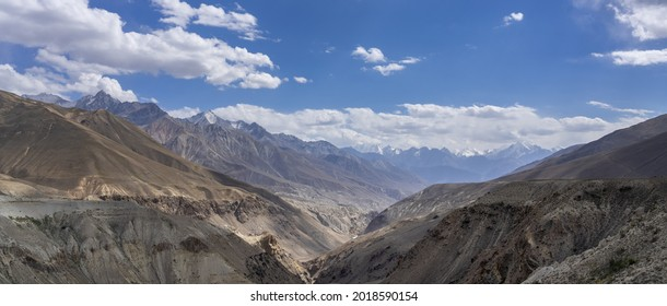 Beautiful panoramic view of high altitude Pamir river valley with snow capped Hindu Kuch mountain range in background, near Langar, Gorno-Badakshan, Tajikistan - Shutterstock ID 2018590154