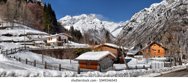 Beautiful panoramic view of historic mountain village on a scenic cold sunny day with blue sky and clouds in winter, Italian region