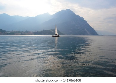 Beautiful panoramic view to the lake Como at Lecco with sailboat moving away from the city at sunset in spring.