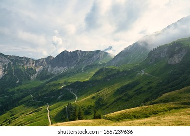 Beautiful panoramic view of the mountains. A curvy hiking trail in a valley. Austrian alps. Hiking adventure.
