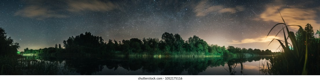 beautiful panoramic view on lake and forest at night looking at stars and milky way passing on center
