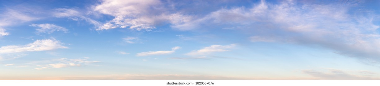 Beautiful Panoramic View of Puffy White Clouds with blue Sky in Background during a sunny summer sunrise. Taken in Yukon, Canada.