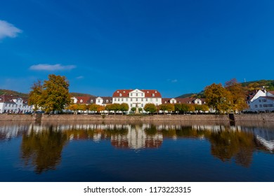 Beautiful panoramic view of a row of baroque houses and the Huguenot Museum in the middle, mirrored on the water surface of the harbour basin on a nice autumn day in Bad Karlshafen, Germany.