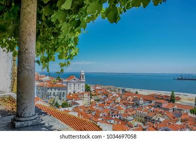 Beautiful panoramic view from Santa Luzia viewpoint (miradouro) to Alfama old town, with Santa Estevao Church, National Pantheon (Santa Engracia Church) and Tagus river, in Lisbon, Portugal.
