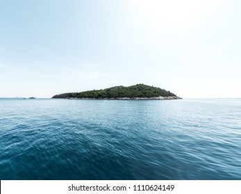 Beautiful panoramic view of the tree covered island of Lokrum in the Adriatic Sea in Croatia with blue sky above and water below.