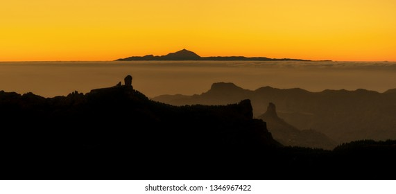 beautiful panoramic view of volcano Teide of Tenerife and Pico Roque Nublo of Gran Canaria during golden sunset