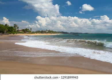 Beautiful paradise view on a beach and waves with deep blue sky and clouds on a sunny day, Tangalle, Sri Lanka