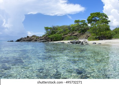 Beautiful paradisiacal Tampico Beach on Caribbean island of Isla Culebra with shallow tranquil water and endemic vegetation on rocky point