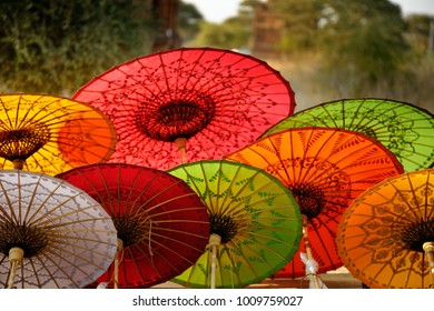 Beautiful parasols in souvenir shop in Myanmar. Hand made umbrellas are back lit, blurred trees and temple in background.