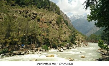 beautiful paravati river flowing through the mountains in kasol
