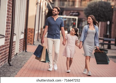Beautiful parents and their cute little daughter are carrying shopping bags, holding hands and smiling while walking down the street