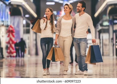 Beautiful parents and their daughter are holding shopping bags and smiling while doing shopping in mall