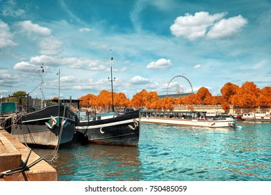 Beautiful Paris in Autumn. Seine riverbank with historical boats moored by the shore and passenger ship passing by. This image is toned.