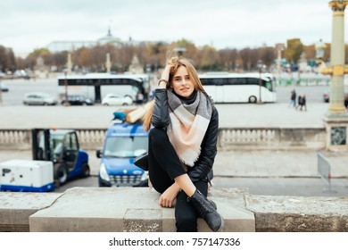 Beautiful parisian girl seating at the stairs with the Eiffel tower background