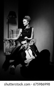 Beautiful passionate couple in classic clothes in the shadows in the room: woman on a chair, a man on the floor at her feet