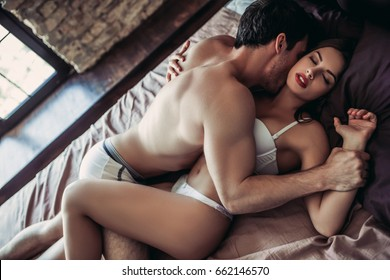 Beautiful passionate couple is having sex on bed. Man is atop.